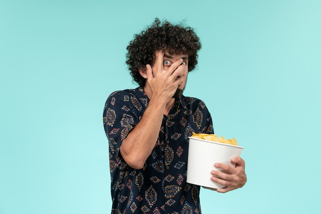 Вид спереди молодой человек, держащий корзину с картофельными чипсами и смотрящий фильм на синем столе, мужской кинотеатр, кинотеатр