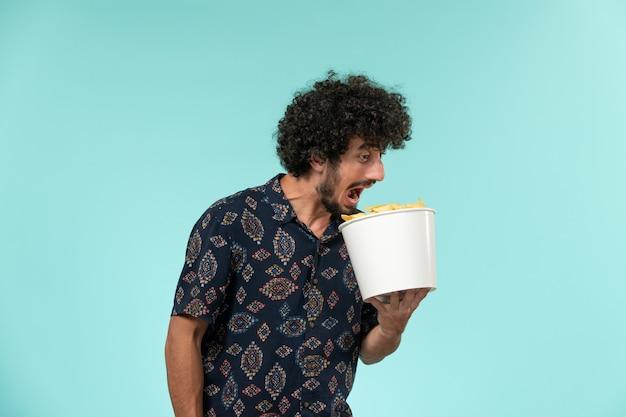 Вид спереди молодой человек, держащий корзину с картофельными чипсами и смотрящий фильм на голубой стене, кино, мужской кинотеатр