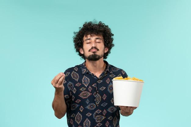 Giovane di vista frontale che tiene il canestro con le patatine fritte sui film maschii remoti del cinema della pellicola dello scrittorio blu