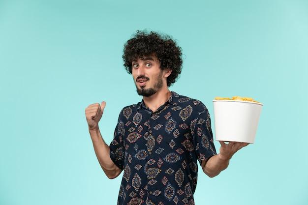 Giovane di vista frontale che tiene il canestro con le patatine fritte su un teatro cinematografico della pellicola di film a distanza della scrivania blu