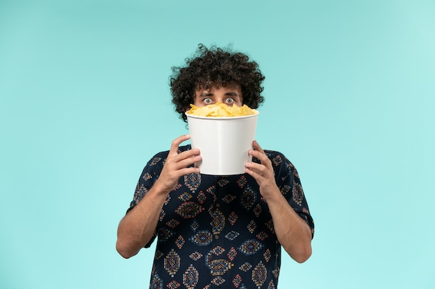 Cestino della tenuta del giovane di vista frontale con le patatine fritte sul maschio del teatro di film di film del cinema di superficie blu
