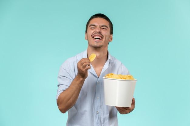 Cestino della holding del giovane di vista frontale con le patatine fritte su un cinema di film a distanza del film della parete blu