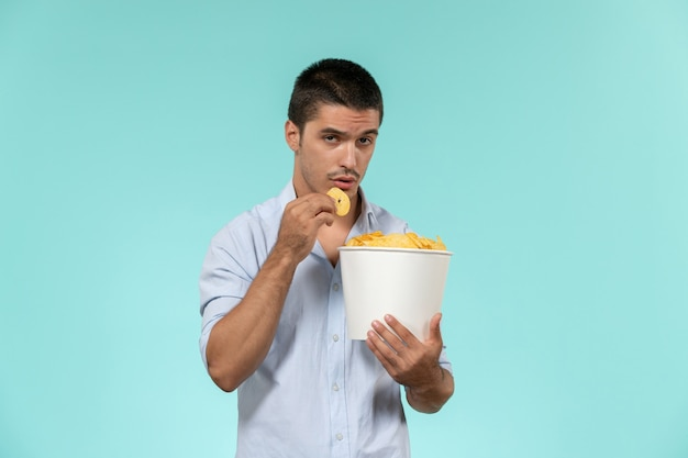 Front view young man holding basket with potato cips on the blue wall film remote movies cinema