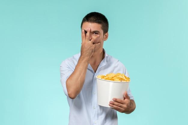 Cestino della holding del giovane di vista frontale con le patatine fritte su un cinema maschio remoto solitario della parete blu