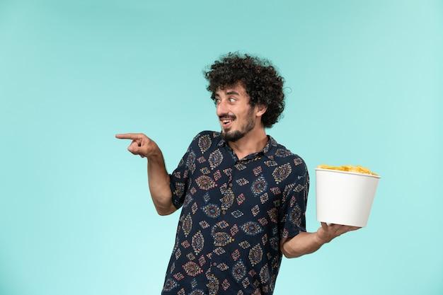 Cestino della holding del giovane di vista frontale con le patatine fritte su un film cinematografico del cinema a distanza della parete blu