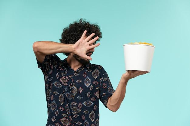 Giovane vista frontale che tiene il cestino con patatine fritte su un muro blu film cinematografici a distanza