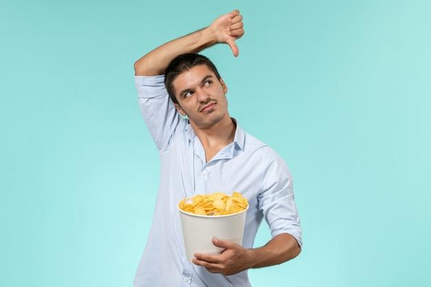 Cestino della holding del giovane di vista frontale con le patatine fritte su un maschio solitario del cinema remoto della parete blu