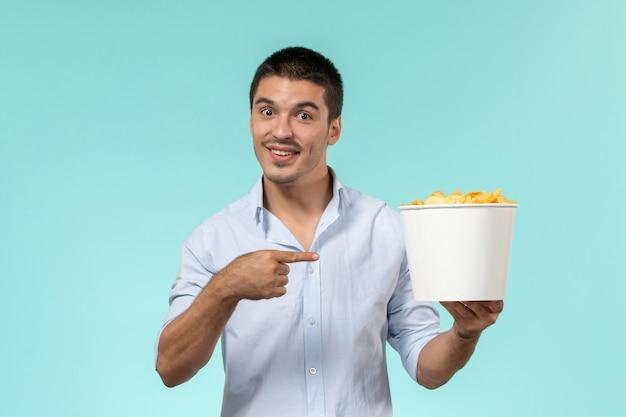 Cestino della holding del giovane di vista frontale con le patatine fritte sul maschio solitario del cinema remoto di film della parete blu