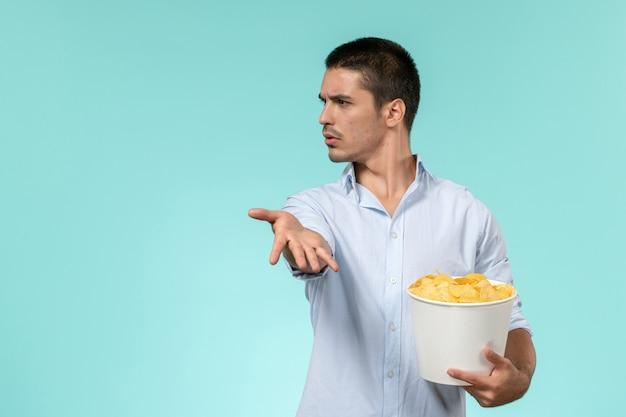 Вид спереди молодой человек, держащий корзину с картофельными чипсами, ест и смотрит фильм на синей стене одинокий удаленный кинотеатр
