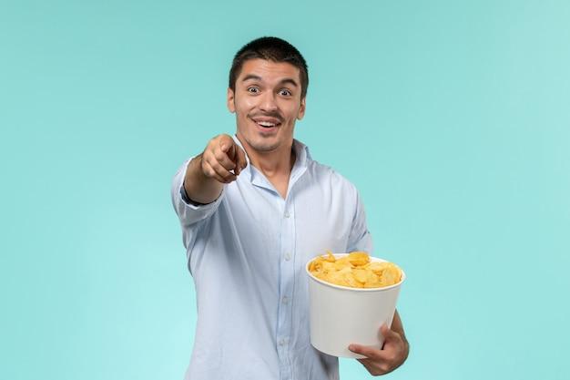 Вид спереди молодой человек, держащий корзину с картофельными чипсами, ест и смотрит фильм на голубой стене одинокий удаленный кинотеатр