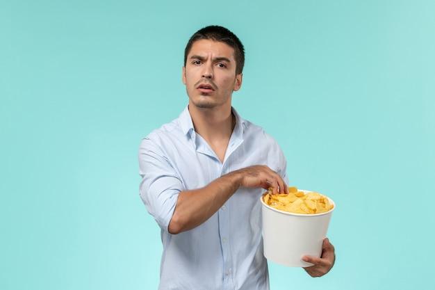 Giovane vista frontale che tiene il cestino con le patatine fritte che mangia e che guarda film sul cinema di film a distanza solitario della parete blu-chiaro