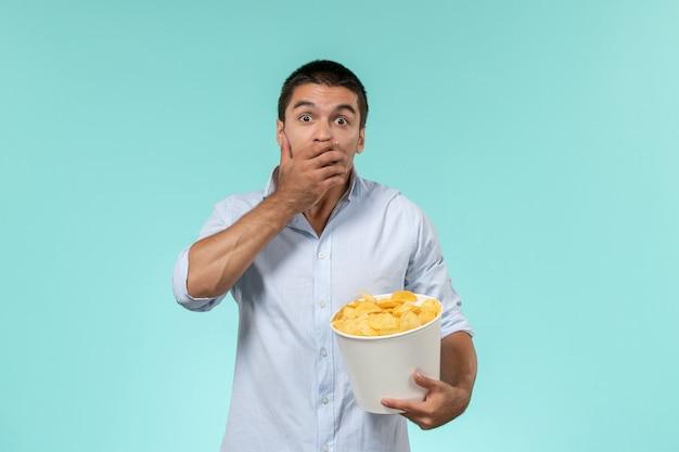 Vista frontale del giovane che tiene il cestino con le patatine fritte che mangia e che guarda film scioccato sul cinema di film a distanza solitario della parete blu
