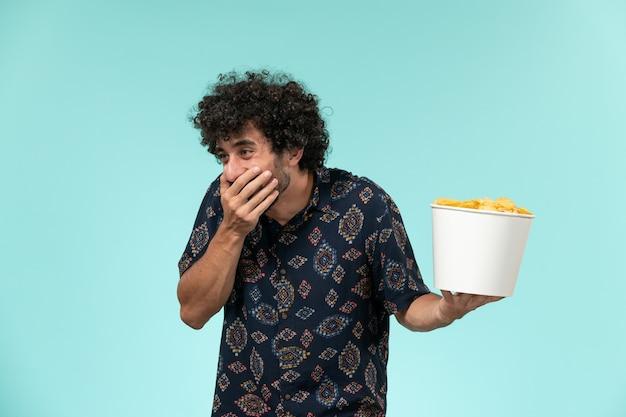 Vista frontale del giovane che tiene il canestro con le patatine fritte e che ride sul teatro di film cinematografici del cinema a distanza della parete blu