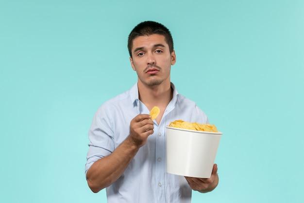 Cestino della holding del giovane di vista frontale con le patatine fritte sul cinema di film a distanza del film della parete blu chiaro