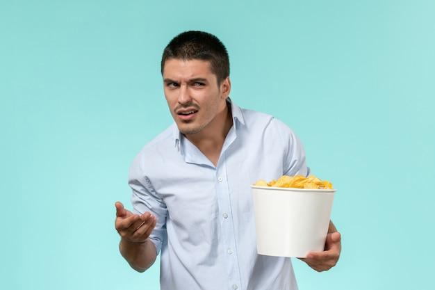 Cestino della tenuta del giovane di vista frontale con le patatine fritte sul maschio solitario del cinema remoto della parete azzurra
