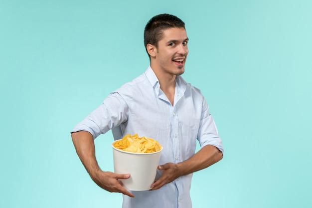 Вид спереди молодой человек, держащий корзину с картофельными чипсами на синей стене одинокий удаленный кинотеатр мужчина