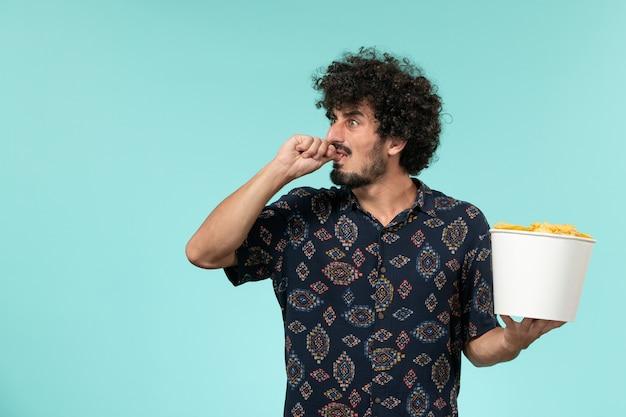 Вид спереди молодой человек, держащий корзину с картофельными чипсами на синей стене удаленного кинотеатра