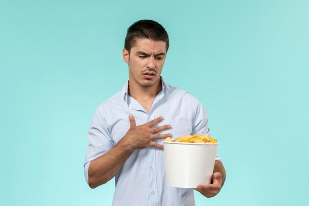 Вид спереди молодой человек, держащий корзину с картофельными чипсами на голубой стене удаленного кинотеатра одинокий мужчина