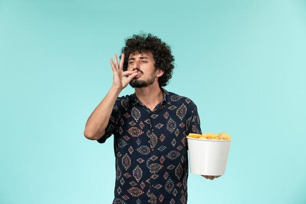 Вид спереди молодой человек, держащий корзину с картофельными чипсами на синей стене удаленный кинотеатр кинотеатр