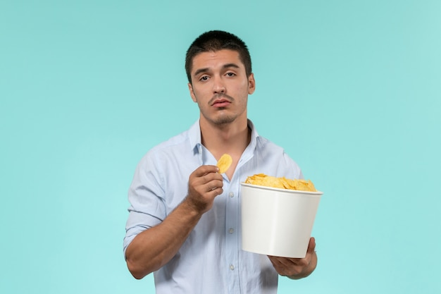 Вид спереди молодой человек, держащий корзину с картофельными чипсами на голубой стене, удаленный кинотеатр