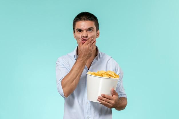 Вид спереди молодой человек, держащий корзину с картофельными чипсами на голубой стене одинокий удаленный мужской кинотеатр