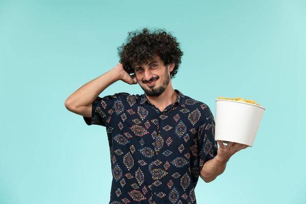 Вид спереди молодой человек, держащий корзину с картофельными чипсами на голубой стене удаленный кинотеатр, кинотеатр