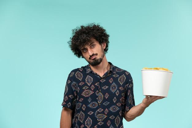 Вид спереди молодой человек, держащий корзину с картофельными чипсами на голубой стене удаленный кинотеатр кинотеатр