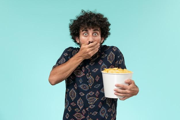 Vista frontale del giovane che tiene il cestino con le patatine fritte e guardare film sul cinema di film cinema parete blu