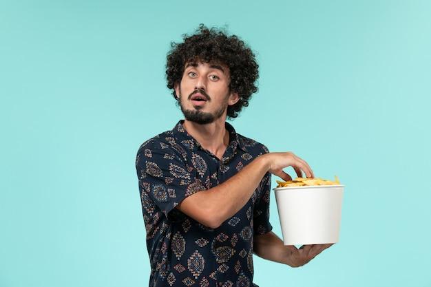 Vista frontale del giovane che tiene il cestino con le patatine fritte e guardare il film sul cinema maschio di film del cinema della parete blu