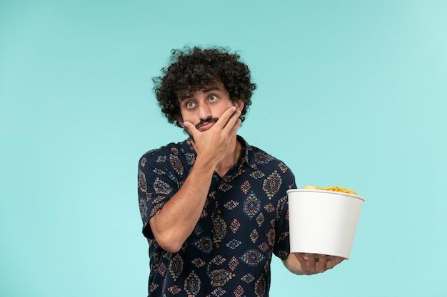 Вид спереди молодой человек, держащий корзину с картофельными чипсами, смотрит фильм, думая на синей стене, удаленный кинотеатр, кинотеатр