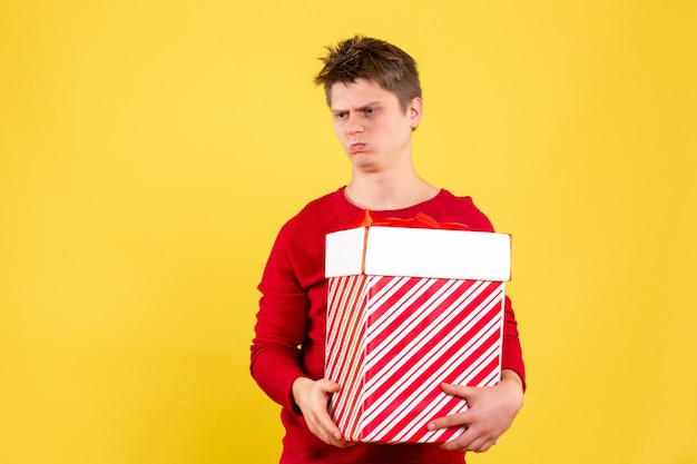 Vista frontale del giovane che tiene grande regalo di natale sulla parete gialla