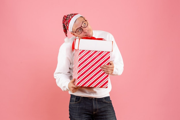 Front view of young man holding big present on pink wall