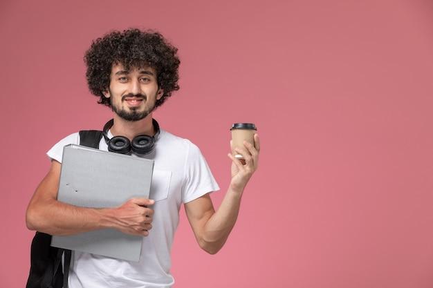 Вид спереди молодой человек, держащий связыватель и чашку кофе