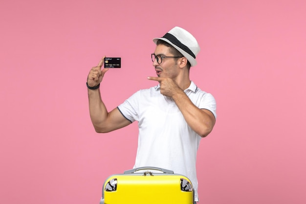 Front view of young man holding black bank card on pink wall