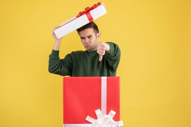 Giovane vista frontale che tiene il coperchio della scatola che fa il segno del thum giù che sta dietro il grande giftbox su giallo
