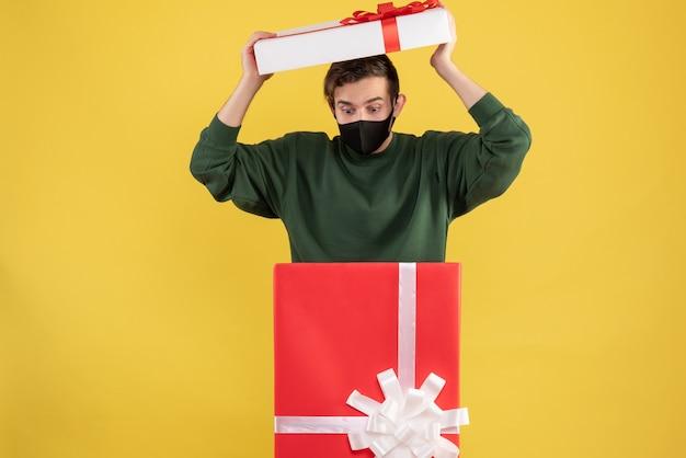 Giovane vista frontale che tiene il coperchio della scatola in piedi dietro il grande giftbox su giallo