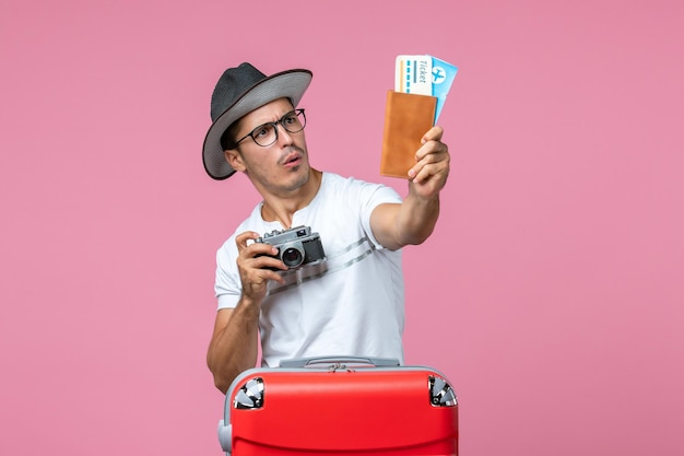 Front view of young man holding camera and plane tickets on pink wall
