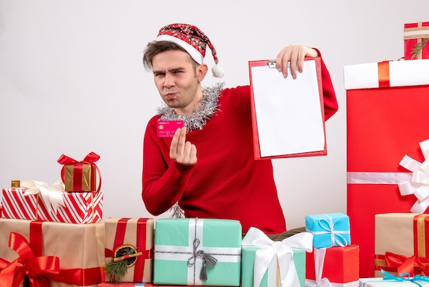 Front view young man holding card and clipboard sitting around xmas gifts