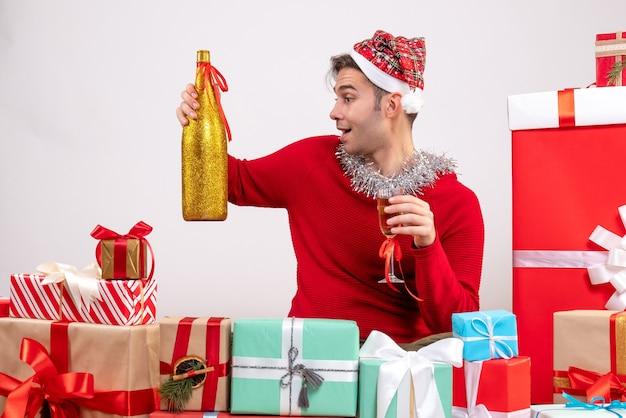 크리스마스 선물 주위에 앉아 샴페인을 들고 전면보기 젊은 남자