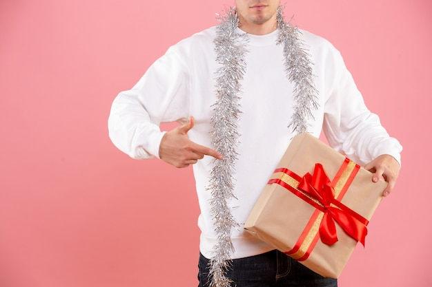 Front view of young man holding christmas present on pink wall
