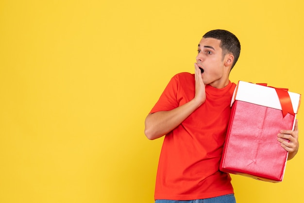 Front view of young man holding christmas present shocked on yellow wall