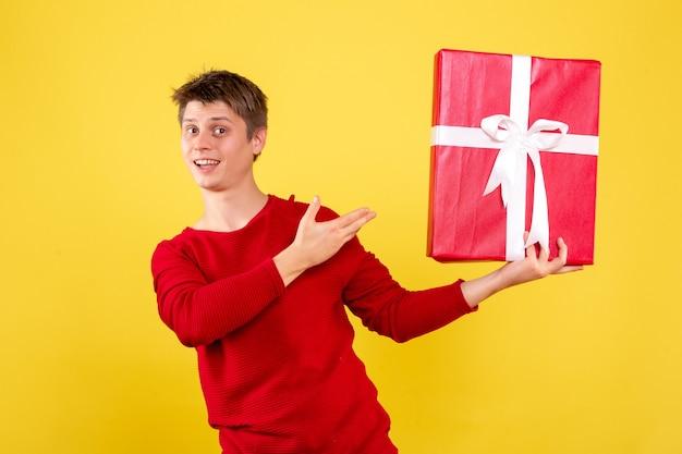 Vista frontale del giovane che tiene regalo di natale sulla parete gialla