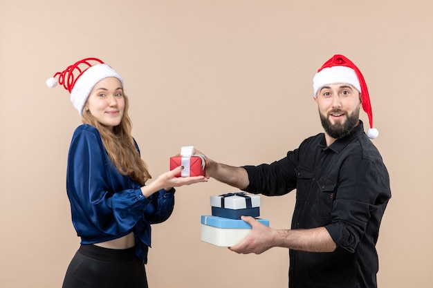 Front view of young man holding christmas presents with woman on pink wall