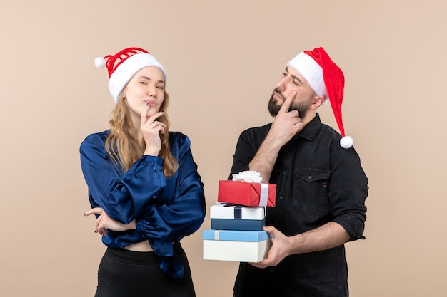 Front view of young man holding christmas presents with woman on the pink wall