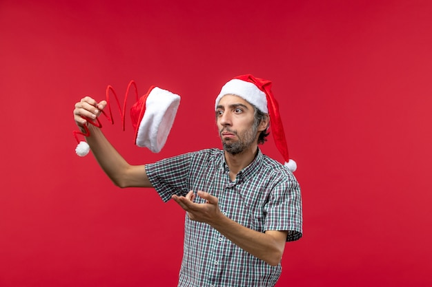 Front view of young man holding christmas toy cap on a red wall