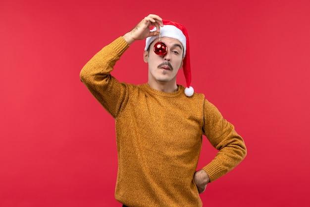 Vista frontale del giovane che tiene il giocattolo dell'albero di natale sulla parete rossa