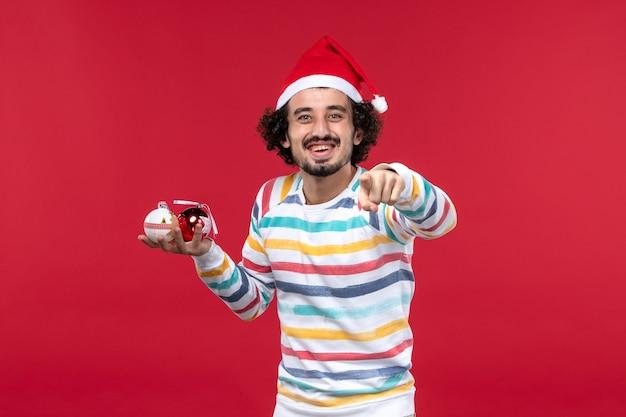 Вид спереди молодой человек держит елочные игрушки на красной стене праздник красный человек