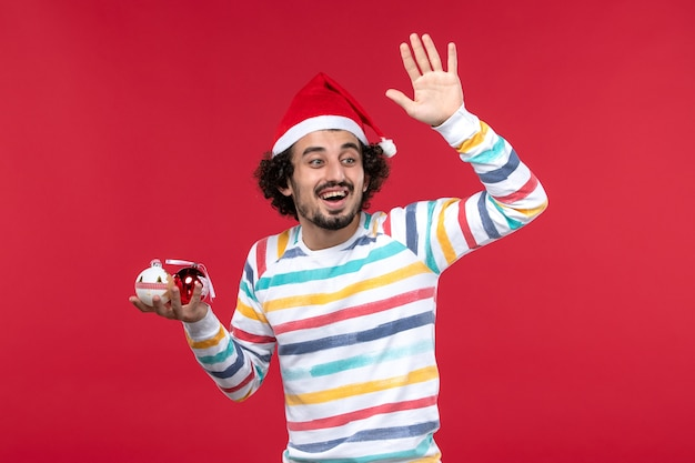 Вид спереди молодой человек держит елочные игрушки на красной стене праздники красный человеческий новый год