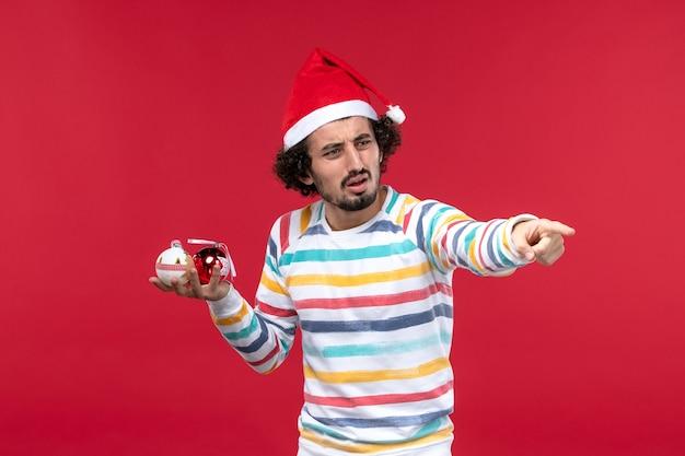 Вид спереди молодой человек держит елочные игрушки на красной стене новый год человеческие праздники красный