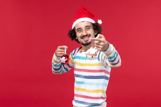 Вид спереди молодой человек держит елочные игрушки на красной стене новогодний красный праздник